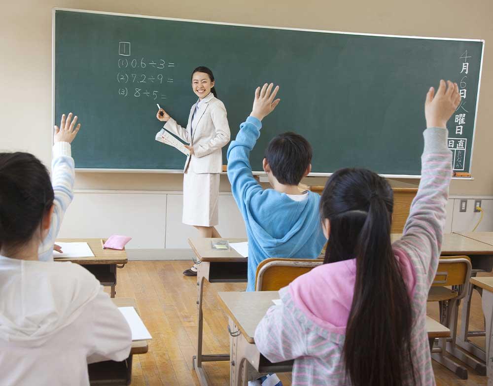 授業風景 教壇に立つ女性教師と手を挙げる子供たち
