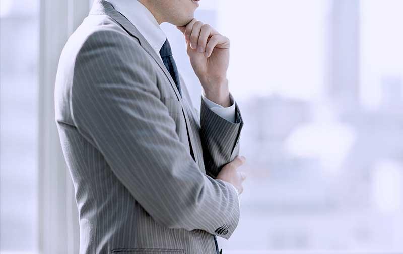 腕を組み考えるスーツの男性〜IT戦略顧問サービスへ