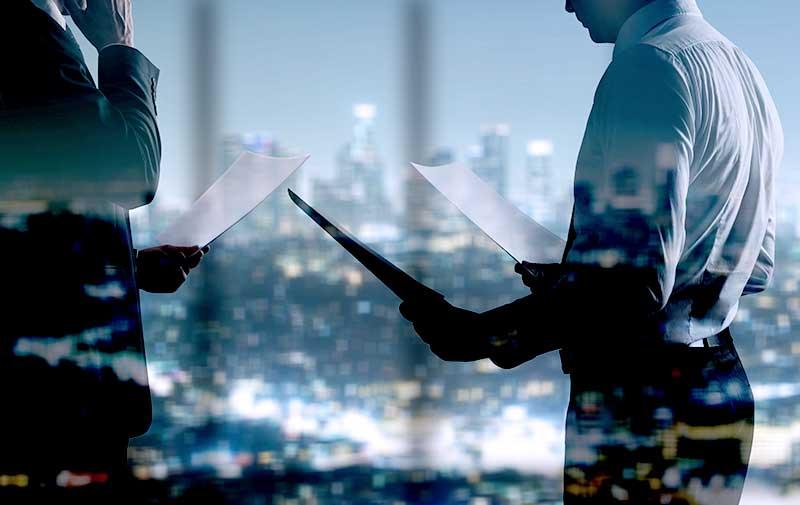 社内で書類を手に打ち合わせる二人の男性〜ITプロジェクト支援サービスへ