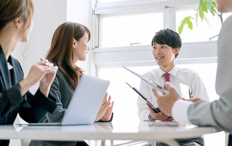 テーブルでプロジェクトの打ち合わせをする男女数名〜IT責任者/リーダー育成サービスへ