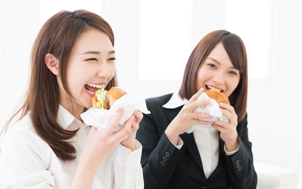 美味しそうにファストフードを食べる女性2名