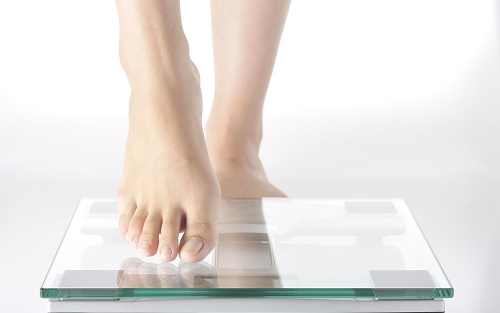 体重計に乗ろうとする女性の足
