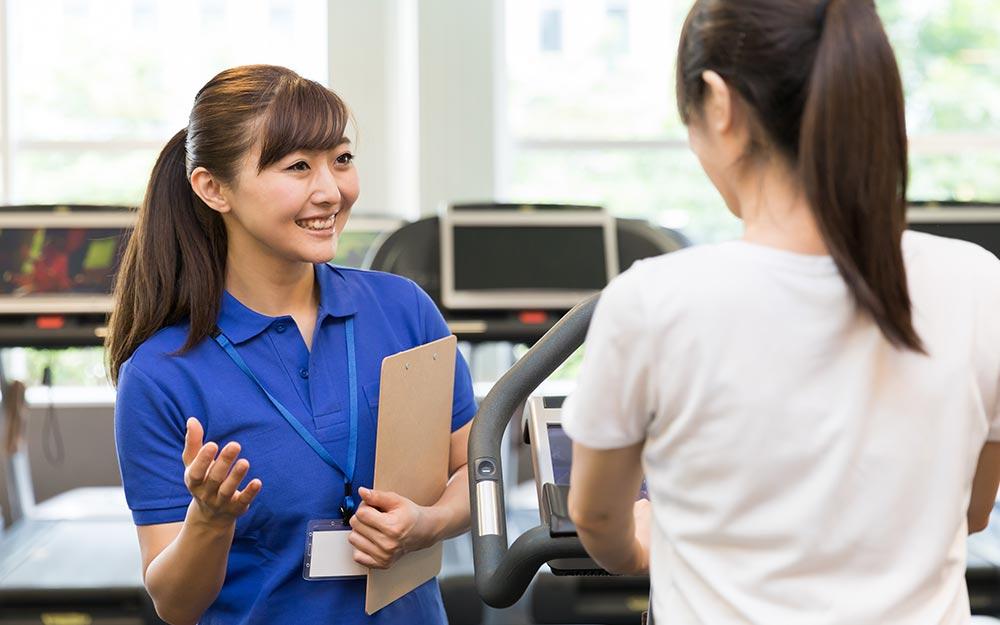 スポーツジムで体調管理を促す女性トレーナー