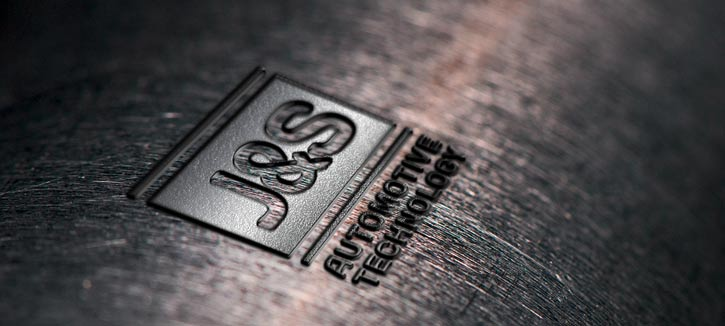 J & S logo engraved in metal