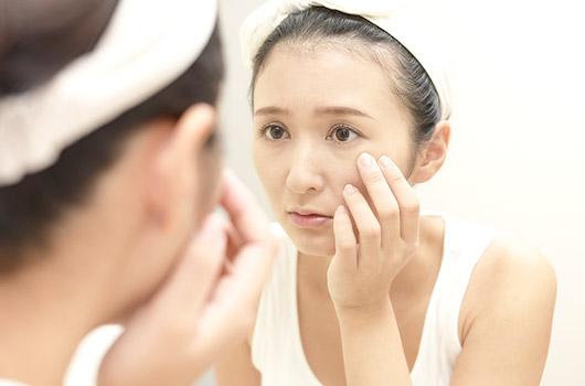 肌荒れを気にしながら鏡を覗き込む女性