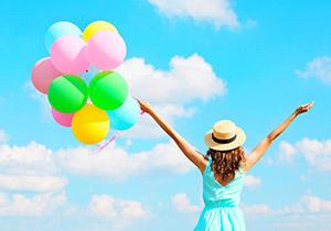手に風船を持ち青空を仰ぐ女性