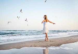 海辺で両手を広げ深呼吸をする女性