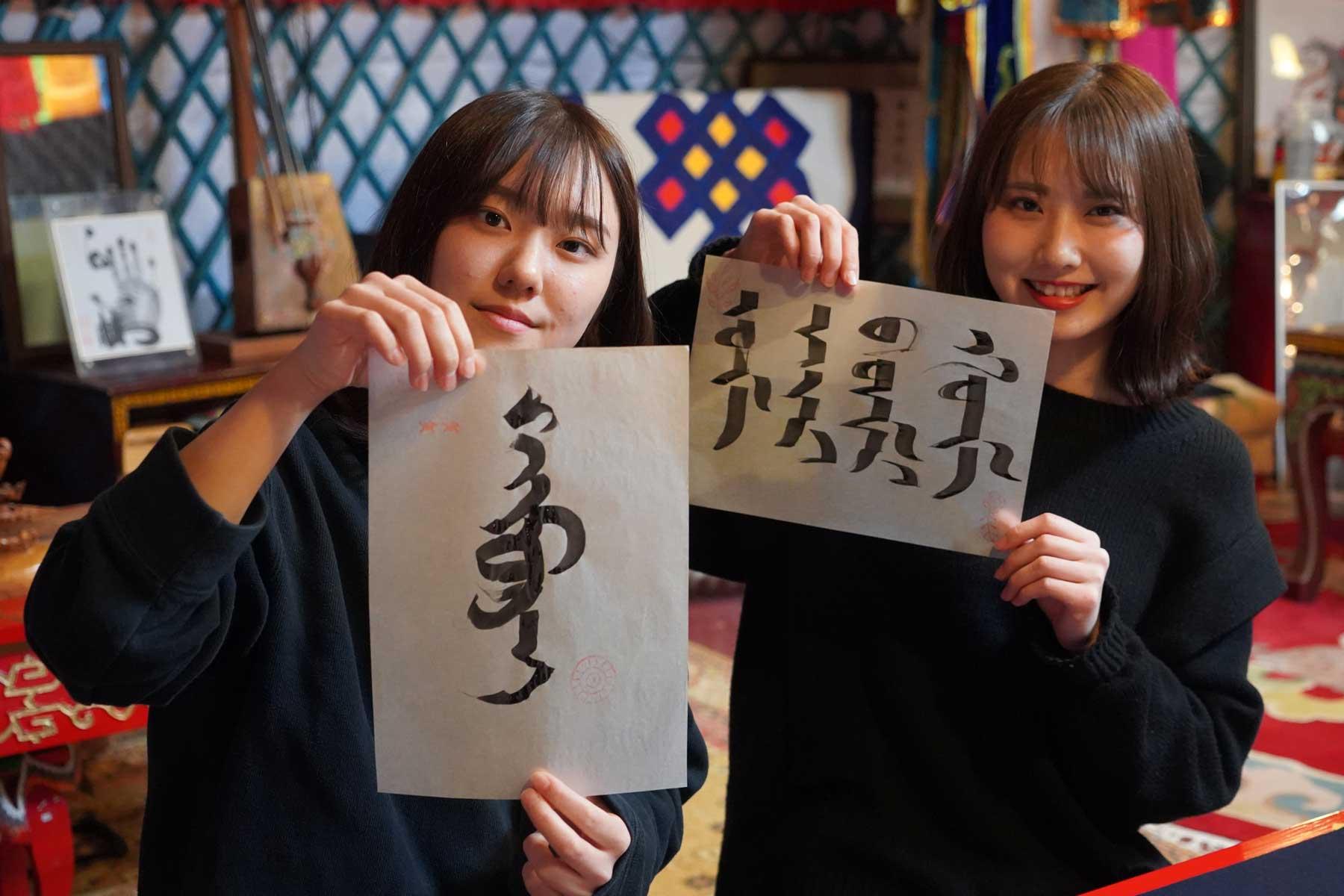 オータニモンゴルの里でのモンゴル文字書道の作品を見せる女の子たち