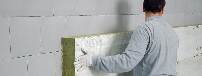 Ein Mitarbeiter der Omega-Spezialbau GmbH klebt WDVS-Platten an eine Fassade