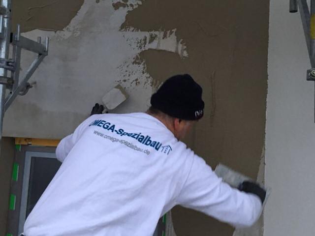 Ein Mitarbeiter der Omega-Spezialbau GmbH beim verputzen einer Fassade