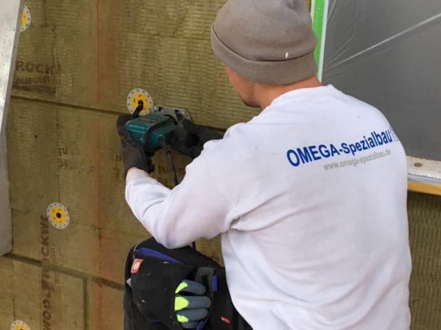Ein Mitarbeiter der Omega-Spezialbau GmbH bei der Fassadendämmung