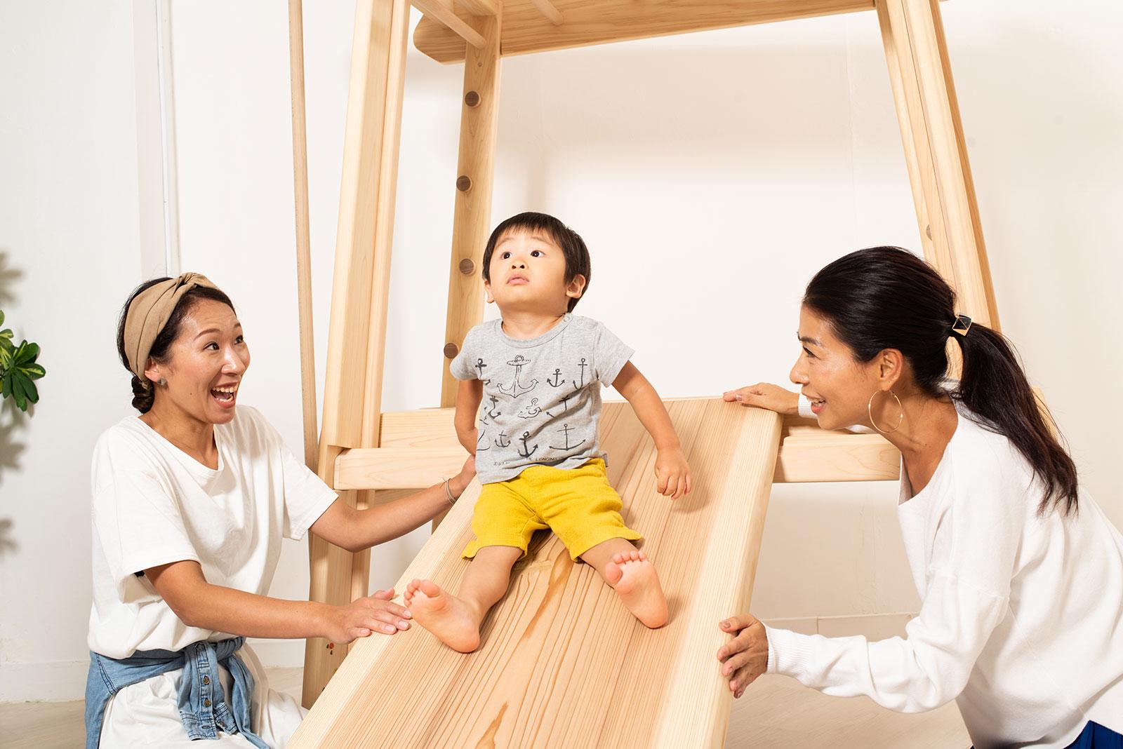 室内雲梯の滑り台で遊ぶ子ども