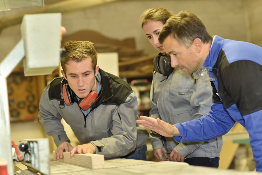 Eine junge Auszubildende und ein junger Auszubildender stehen mit Ihrem Ausbilder an einem Holztisch und lernen das Schreinerhandwerk. Alle drei trgan zur Fachkräftesicherung im Landkreis Heidekreis bei.