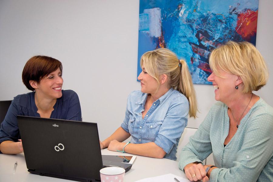 Drei Frauen sitzen lächelnd mit einem Laptop an einem Tisch