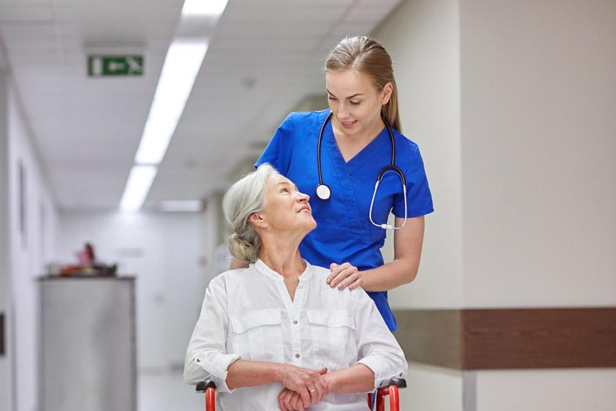 Eine ältere Dame sitz in einem Rollstuhl und lächelt die hinter ihr stehende junge Pflegerin an, die ihr mutmachend die Hand auf die Schulter gelegt hat.