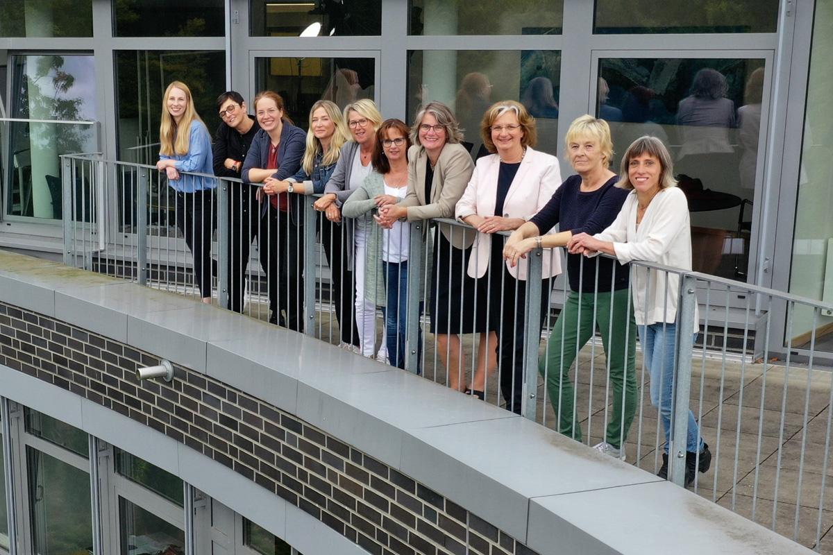 Zehn Mitarbeiterinnen der Wirtschaftsförderung Heidekreis stehen sympatisch lächelnd an das Geländer des Balkons des Verwaltungsgebäudes des Landkreises gelehnt.