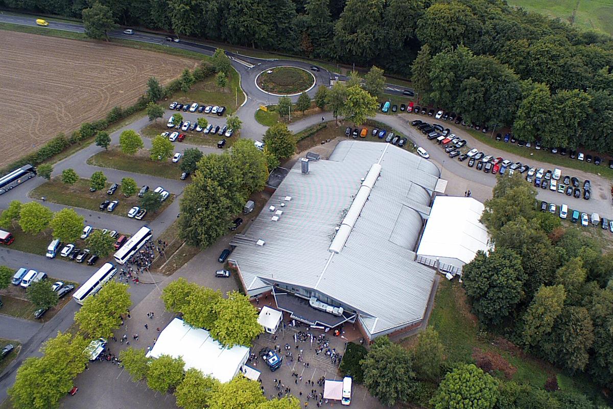 Blick auf die Heidmarkhalle Bad Fallingbostel aus der Vogelperspektive. Drumherum ein mit Autos gefüllter Parkplatz. Mehrere Messebesucher stehn vor dem Eingang.