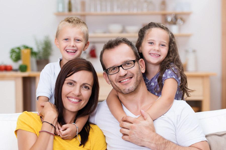 Eine junge Familie mit zwei kleinen Kindern gemeinsam zuhause fröhlich auf dem Sofa