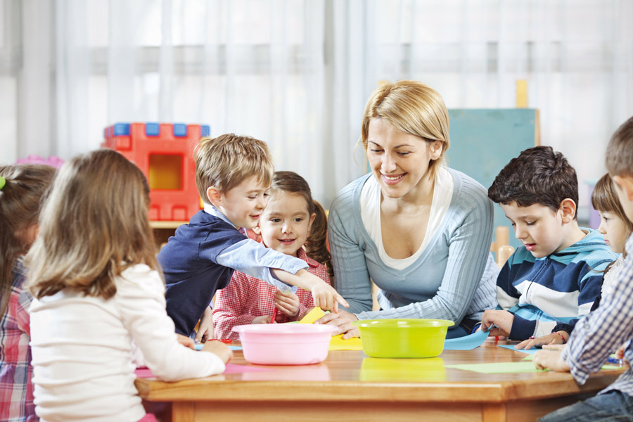 Eine fröhliche Kinderbetreuerin kümmert sich liebevoll um sechs kleine Kinder, alle zusammen sitzen um einen Tisch herum und spielen..