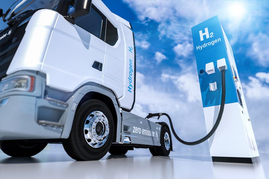 Weiß lackierter LKW steht angeschlossen an einer blau- weißen Wasserstoff-Aufladestation mit der Aufschrift H2 Hydrogen.