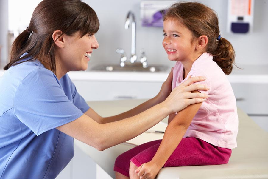 Ein lkeines Mädchen sitzt lächelnd in einem Behandlungszimmer auf einer Liege. Vor ihr sitzt eine lächelnde Ärztin.