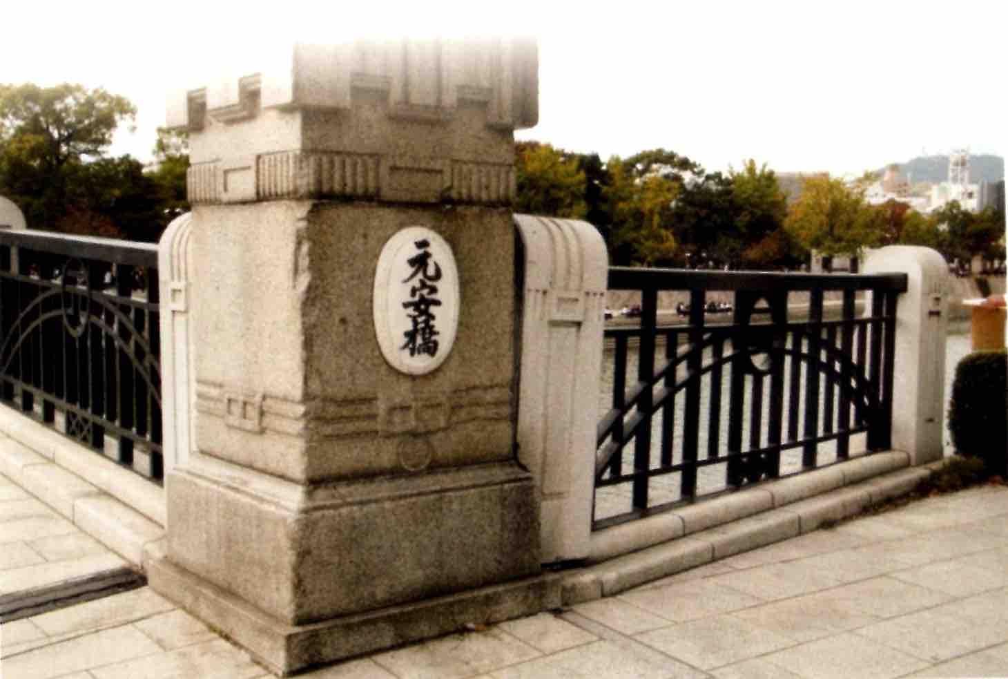 広島市の元安川にかかる橋、「もとやすばし」。橋の名前が親柱に漢字で書かれている。この橋は爆心地の原爆ドームの少し南にある。原爆の投下目標とされた、「あいおいばし」の一本南にかかる橋。出典は書籍『神秘の大樹 第二巻 ヒロシマとつる姫』