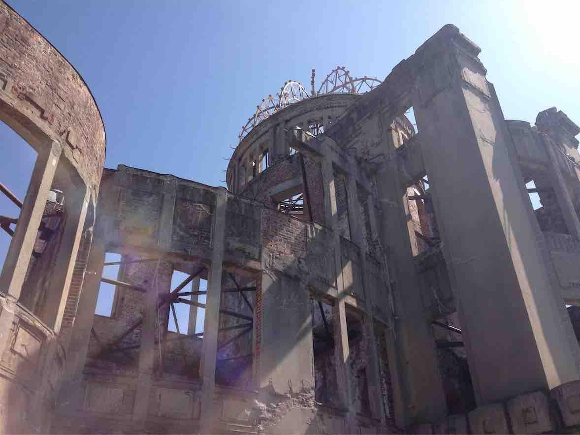 広島市の原爆ドーム。そばでドーム全体を見上げるように撮影された写真。付近から。右上から太陽の光が当たって建物凹部に凸部の影が落ちているとともに、虹が写っている。(このサイト編集者撮影)