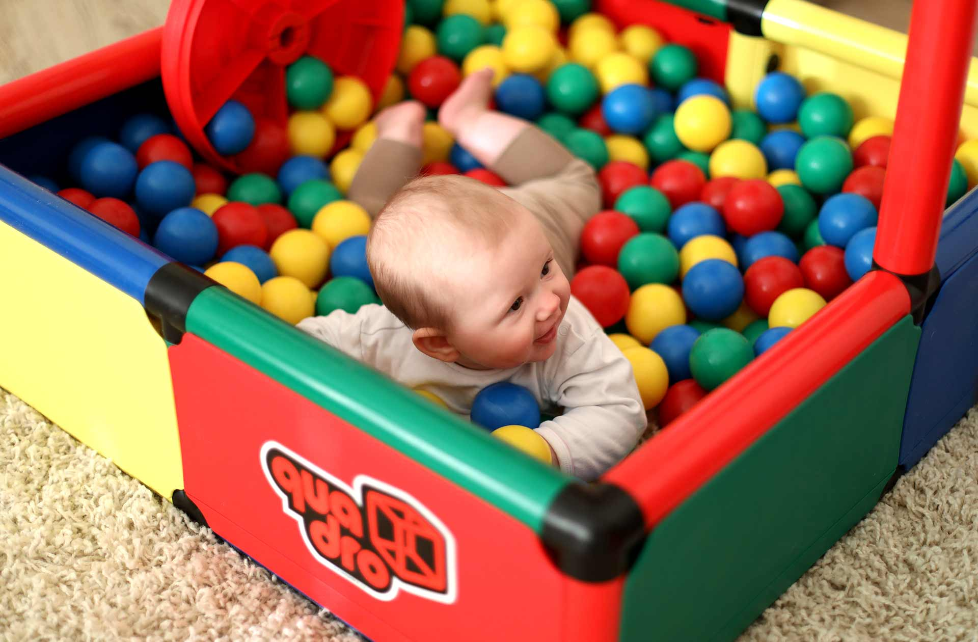 Baby playing in QUADRO ball bath in living room