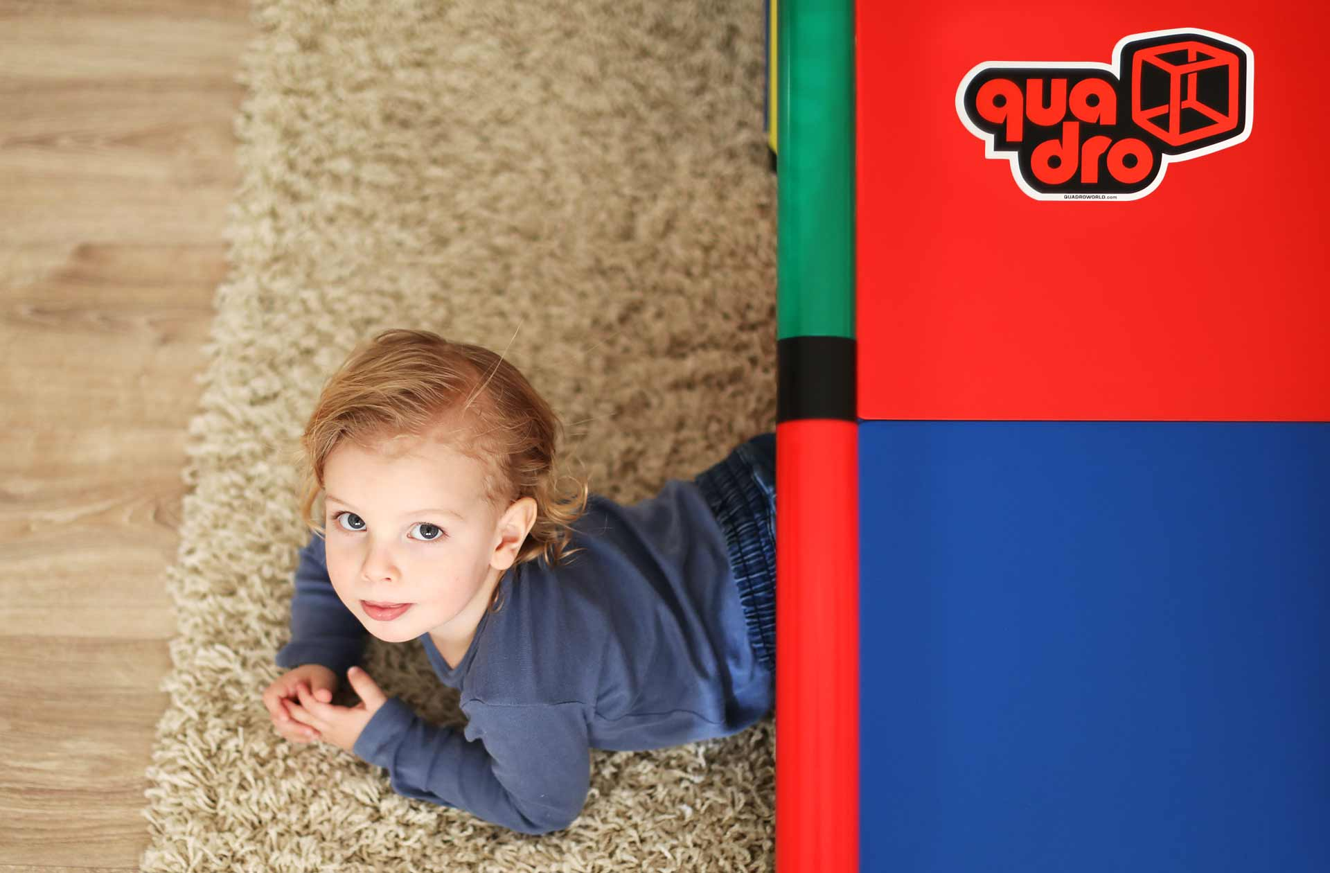Little girl crawling under QUADRO playset in living room