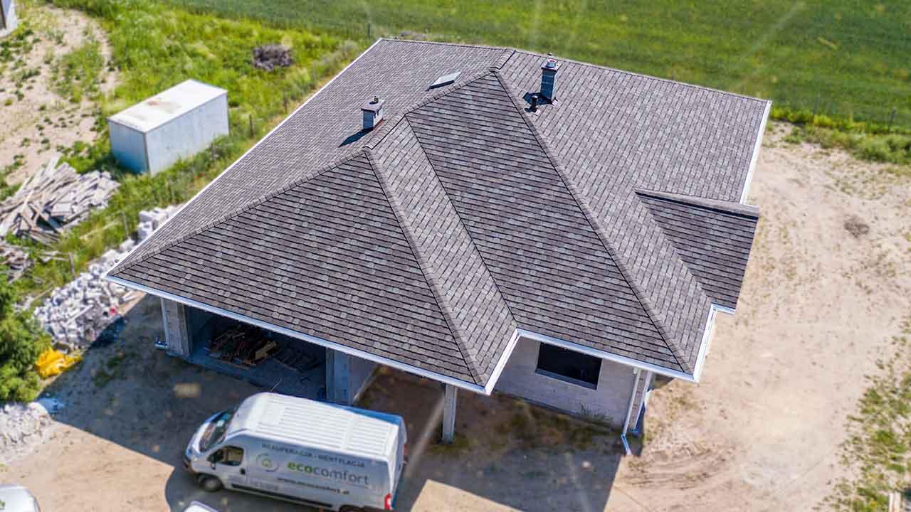 Film z drona prezentuje przepiękny parterowy dom na którym zamontowaliśmy luksusowe pokrycie dachowe jakim jest gont bitumiczny o nazwie Camelot 2 w kolorze Weathered Timber wyprodukowany w USA. Przedstawiony budynek znajduje się w okolicach Poznania