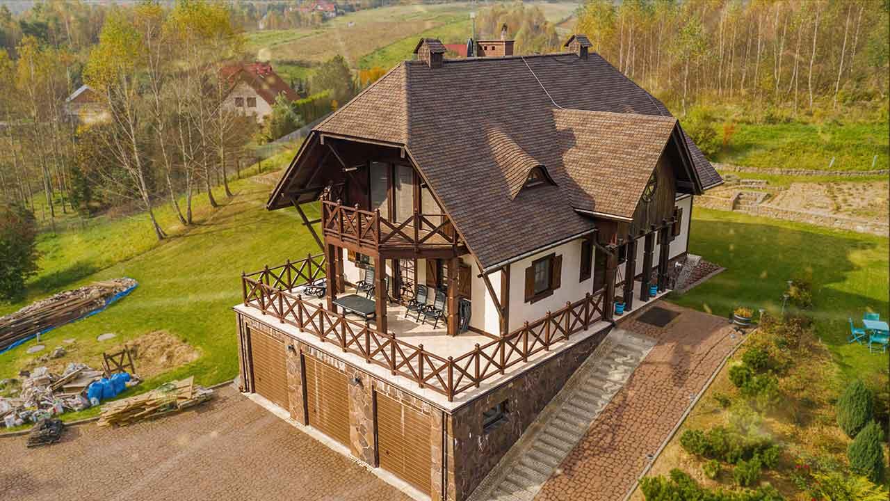 Film z drona przedstawia: Na dachu można zaobserwować prestiżowe pokrycie dachowe, które stylem nawiązuje do gontu drewnianego i jest to gont bitumiczny amerykańskiego producenta GAF model o nazwie Glenwood w kolorze Autumn Harvest. Dach znajduje się w okolicach Krakowa