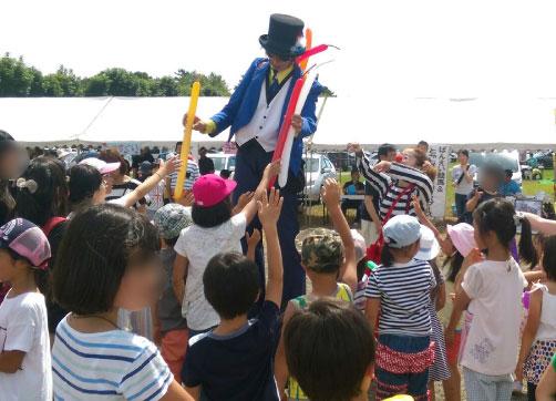 バルーンを子供達に渡すシルクハット姿の男性
