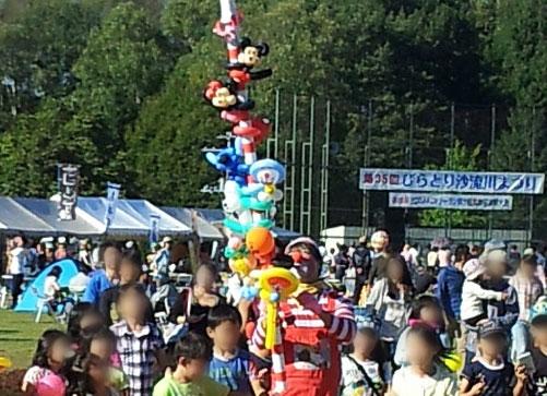 高さのあるバルーンアートを持って歩くピエロとその周りに群がる子供達