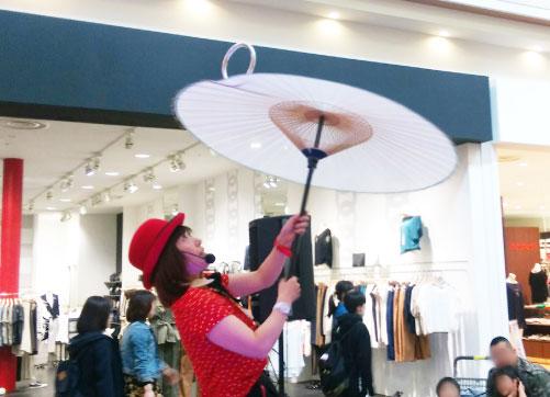 傘で芸を披露する女性