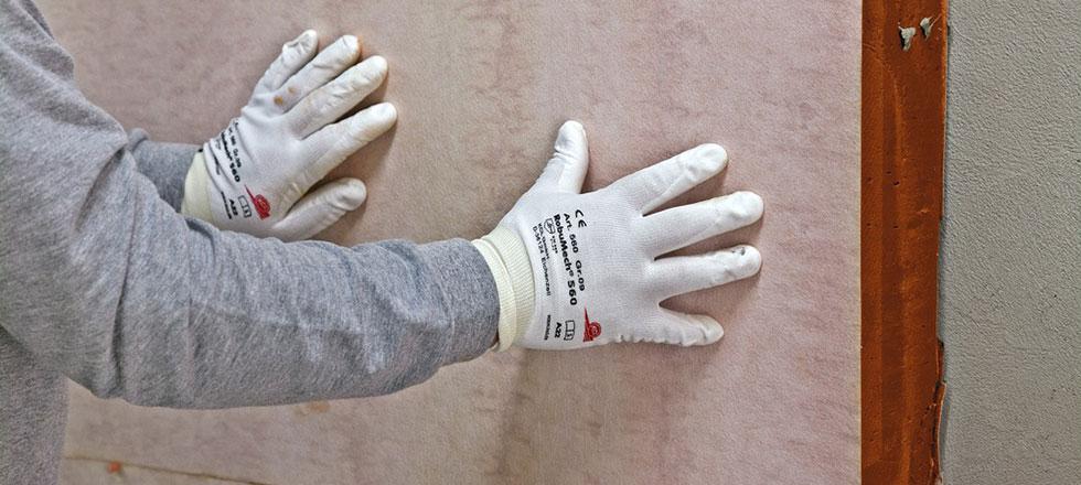 Ein Mitarbeiter der 3B Denkmalpflege & Bausanierung beim verkleben einer WDVS Dämmplatte.