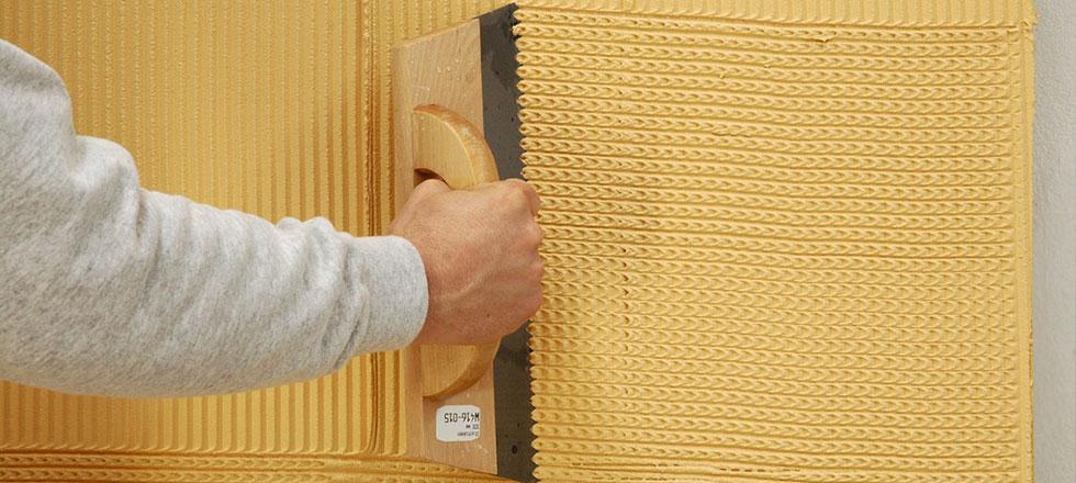 Ein Mitarbeiter der 3B Denkmalpfelge & Bausanierung GmbH verputz eine Fassade.